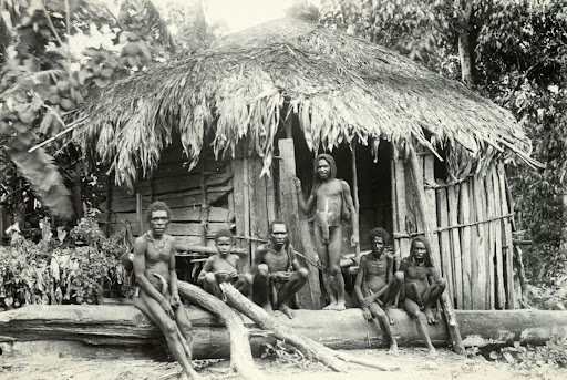 Dem Papuans in front of the men's house