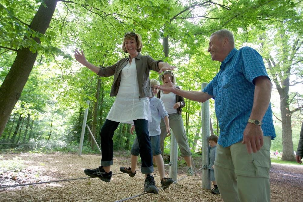 Du siehst mehrere Menschen verschiedenen Alters, die versuchen auf dünnen Drähten zu balancieren.