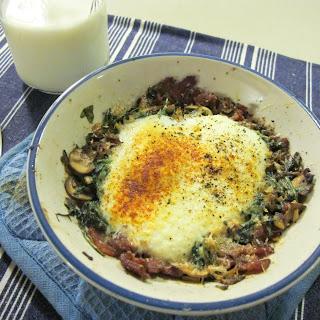 Parmesan Baked Eggs Over Bacon, Mushroom, Leek, And Arugula Hash