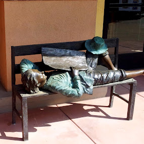by Tom Carson - Buildings & Architecture Statues & Monuments ( bronze, drowsy, statue, bench, sunshine, laying, sleeping, loitering, snooze, barefoot, newspaper, hat )