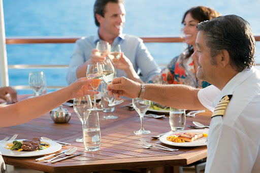 Tere-Moana-LaVeranda-captain-toast - Clink glasses with the ship's captain in La Veranda when Tere Moana pulls into port. The restaurant features floor-to-ceiling windows and indoor and al fresco seating.