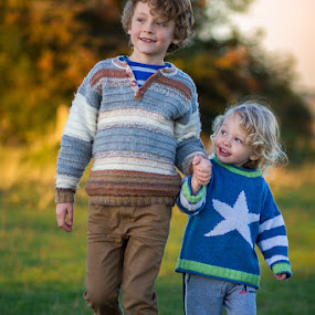 young brothers holding hands by Keren Woodgyer - Babies & Children Child Portraits ( walking, photograph, holding, blond, little, children, travel, people, caucasian, looking, child, love, curly, hands, autumn, family, adoration, toddler, hair, smiling, footsteps, brothers, affection, grass, admiring, togetherness, dusk, up, admiration, traveling, sunset, sibling, outdoors, trees, big, boy, adore, holding hands )