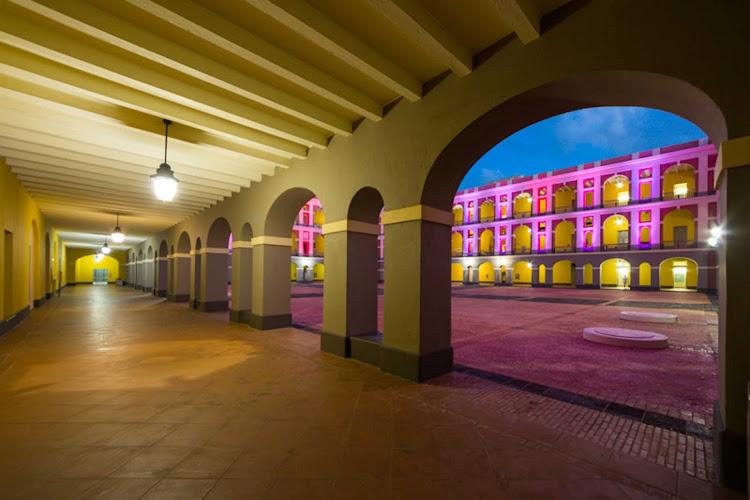 The Ballajá Barracks light up in the twilight in Old San Juan, Puerto Rico.