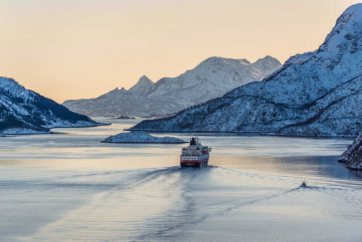Hurtigruten's expedition ship Richard With sails down the Raftsundet strait in Nordland, Norway, into a winter sunset.