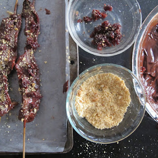 CHOCOLATE COVERED BACON ON A STICK WITH MARCONA ALMONDS AND DRIED CHERRIES.