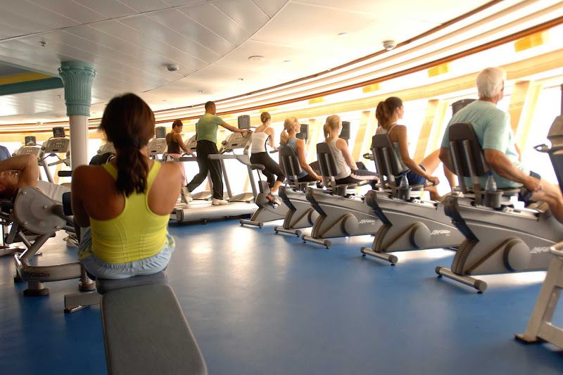 Guests work out on cycles, treadmills and other equipment in the Fitness Center aboard a Disney cruise.