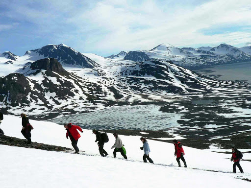Arctic-Spitsbergen-Mountains-Landscape-Travellers-Hiking - A group of hikers hiking the Spitsbergen Mountains on a G Adventures expedition in Spitsbergen, Norway.