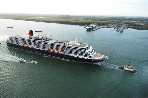 A tugboat leads Queen Victoria to its home port of Southampton, England.