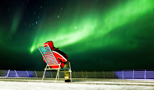 hurtigruten-northern-lights-5 - A guest pulls up a front row seat to the Northern Lights aboard a cruise on Hurtigruten's Finnmarken between the northern ports of Kirkenes and Tromsø.