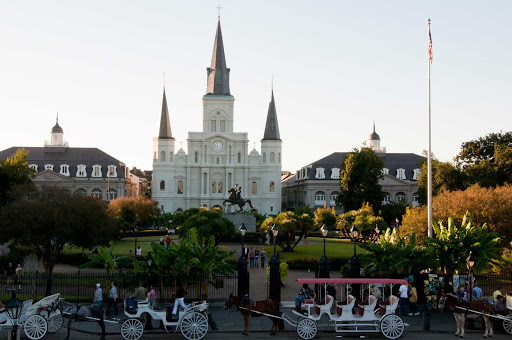 Horse-drawn carriages pull up to Jackson Square in New Orleans.