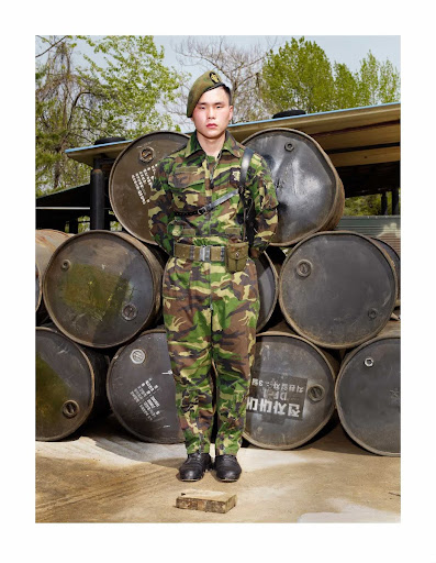 A soldier standing in front of oil drums, May 2010