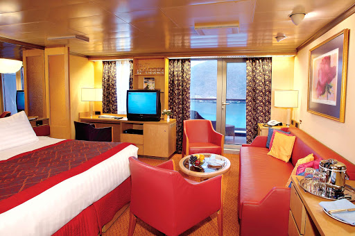 Holland-America-Noordam-Signature-Suite - At 372–384 square feet, Signature Suites on Noordam come with two twin beds convertible to a queen bed, bathroom with dual vanity sinks, whirlpool bath, shower, sitting area, private balcony, sofa bed, floor-to-ceiling windows, TV and mini-bar.