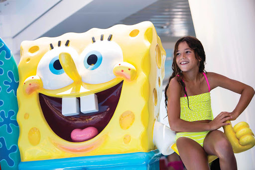 Norwegian-Cruise-Line-Nick-Pool - A girl poses for a photo with SpongeBob in the Aqua Park pool aboard Norwegian Breakaway.