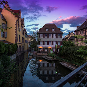 The Vew From The Bridge by Lillian Molstad Andresen - Buildings & Architecture Places of Worship ( clouds, water, colmar city, reflections, landscape, waterstream, city, lights, architectures, sky, nature, bushes, sunset, buildings, trees, watercanal, france, bridge, flowers, colmar, , Urban, City, Lifestyle, purple, yellow, color )
