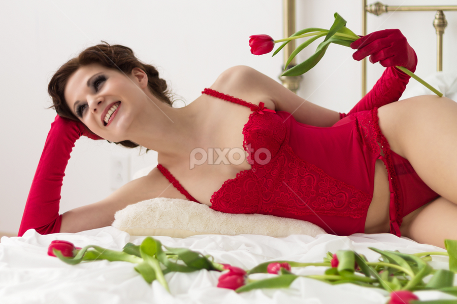 A lady in red by Vikram Mehta - People Portraits of Women ( red, bed, lingerie, woman, gloves, white, pillow, bright, lady, corset, roses, smile )