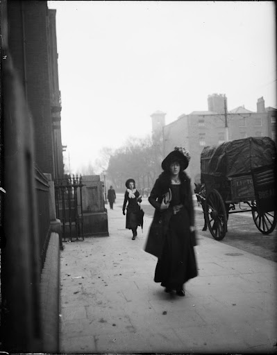 Woman walking past St. Vincent's Hospital, 55-59 St. Stephen's Green. Second woman in the background, horse and cart to the right. Italianate tower of the university building can be seen in silhouette in the background.