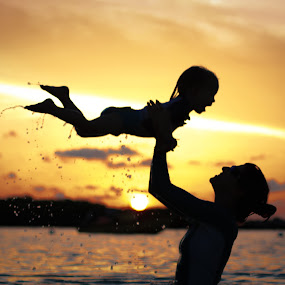 by Troy Wheatley - People Family ( water, playing, sunset, silhouette, mom with kids, #8rtcoMagazine )