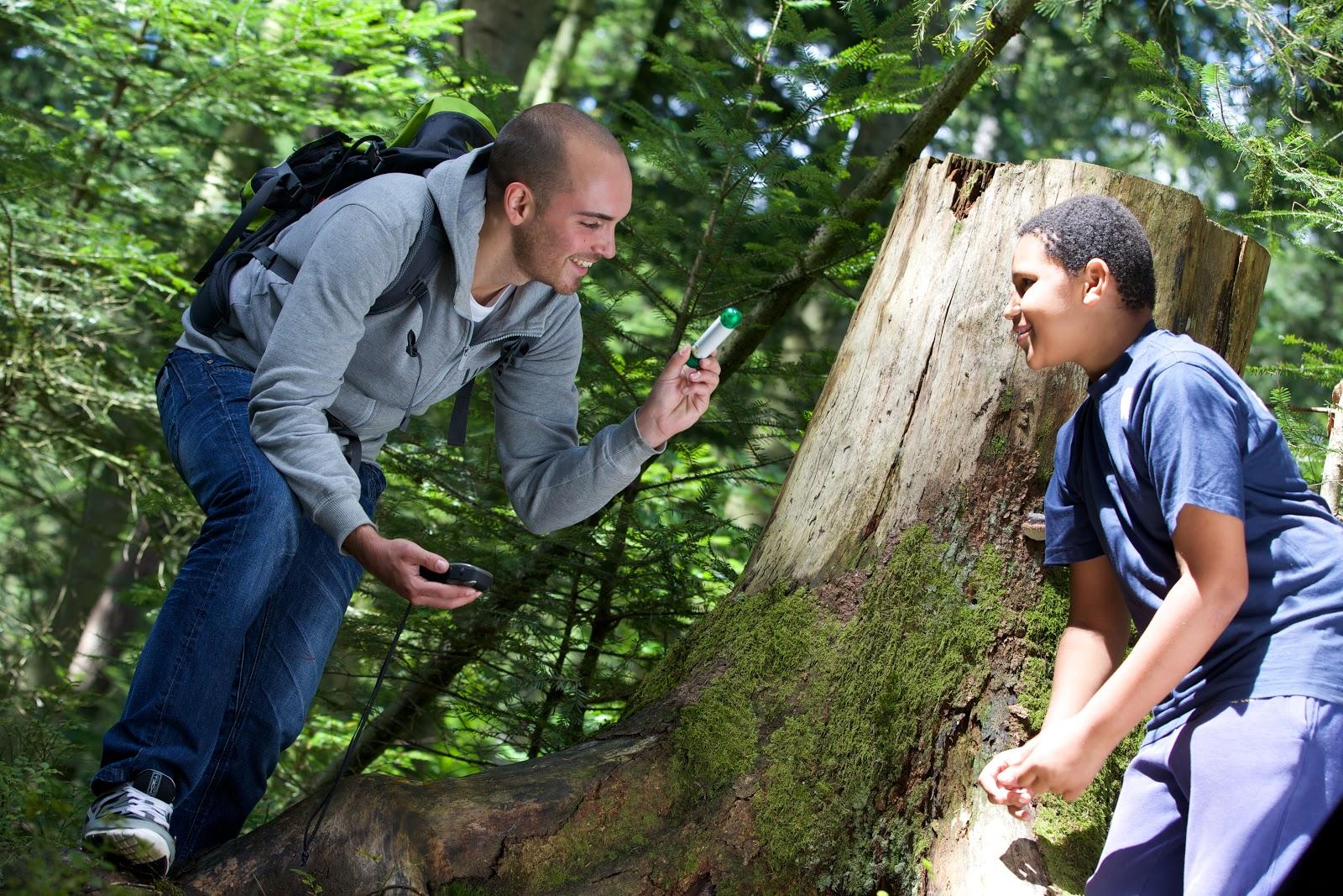 Hier siehst Du zwei junge Männer im Wald mit einem GPS-Gerät in der Hand