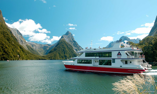 Explore_Milford_Sound - A guided cruise lets you slide between the vertical mountains that form the sides of Milford Sound, New Zealand's most famous fjord. The sheer rock faces are decorated with ancient mosses, lichen, ferns, native trees and tumbling waterfalls.