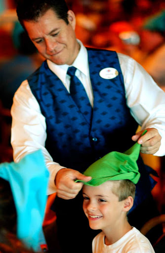 Disney-Dream-boy-and-server - A boy gets fitted for a Robin Hood cap by a server during lunch on Disney Dream.
