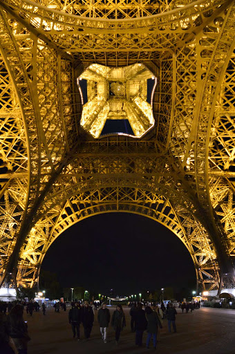 Eiffel-Tower-panorama-Paris - A view of the base of the Eiffel Tower in Paris at night.