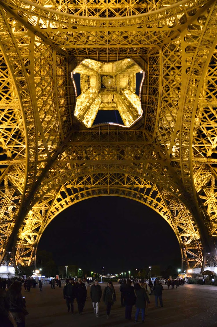 A view of the base of the Eiffel Tower in Paris at night.