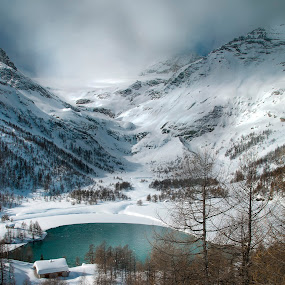 Bernina Pass by Christian Diboky - Landscapes Mountains & Hills ( grisons, larix, bernina, lonely house, white, engadin, lake, graubünden, pass, val poschiavo, bernina pass, poschiavo, winter, blue, snow, dramatic, cloudy, switzerland, brown, larch, lonely, , cold )