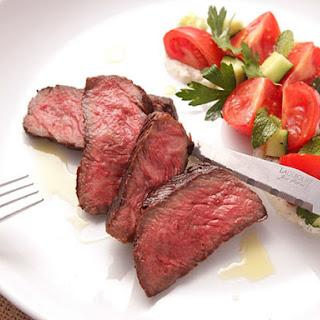 Grilled Strip Steak with Creamy Yogurt Sauce and Tomato-Cucumber Salad.