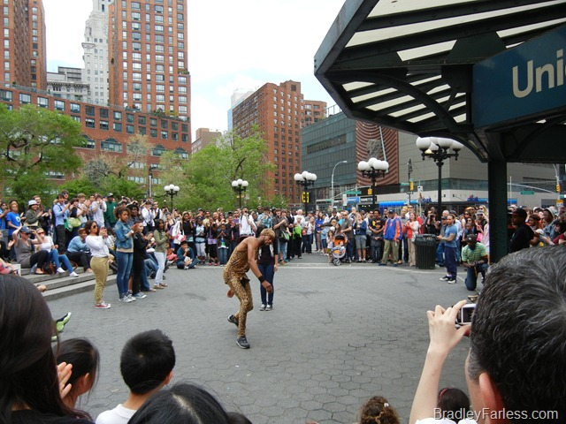 Man in a leopard outfit jumping over a girl in Union Square.