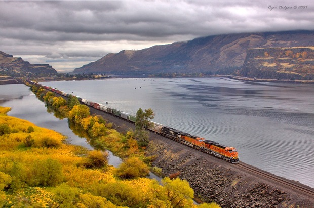 A west bound BNSF manifest train crosses the fill at Chamberlain Lake near Lyle, Washington.
