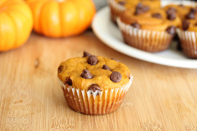 photo of a pumpkin muffin with more on a plate in the background