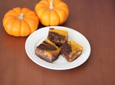 overhead photo of a plate of brownies on a plate with two small pumpkins in the background