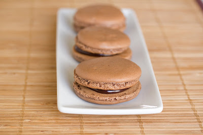photo of chocolate macarons lined up on a plate