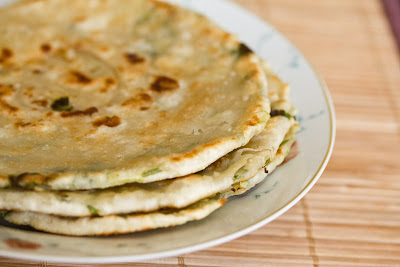close-up photo of a stack of scallion pancakes on a plate