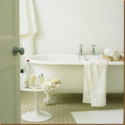 Modern home: white bathroom, roll top bath, honeycomb mosaic vinyl flooring,  round marble top table,  toiletries,  towels. Pub orig  L etc 05/2005 p118