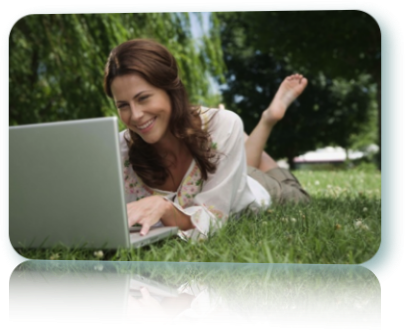 A woman lying in the grass using a lap top.