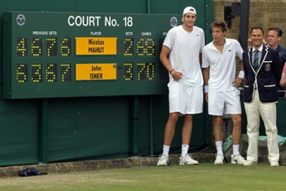 LONDON, ENGLAND - JUNE 24:  John Isner of USA (L) poses after winning on the third day of his first round match against Nicolas Mahut of France (C) with Chair Umpire Mohamed Lahyani on Day Four of the Wimbledon Lawn Tennis Championships at the All England Lawn Tennis and Croquet Club on June 24, 2010 in London, England. The match is the longest in Grand Slam history.  (Photo by Hamish Blair/Getty Images)