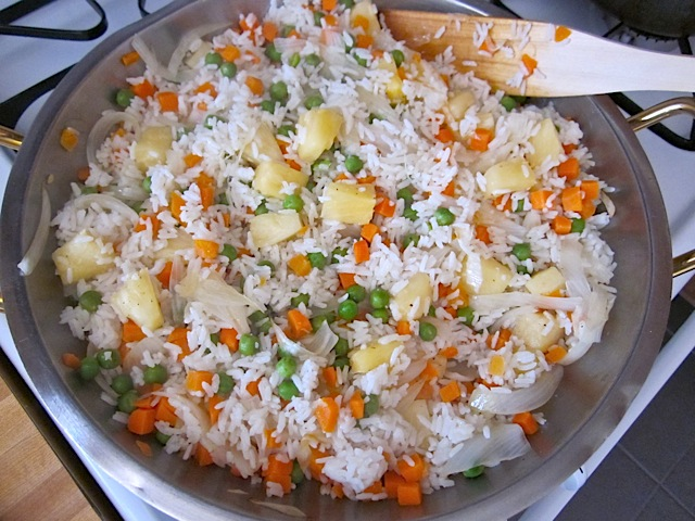 rice and veggie mixture added together in pan with wooden spoon