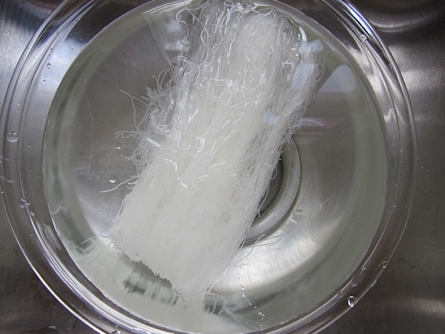 soaking rice noodles in bowl of water