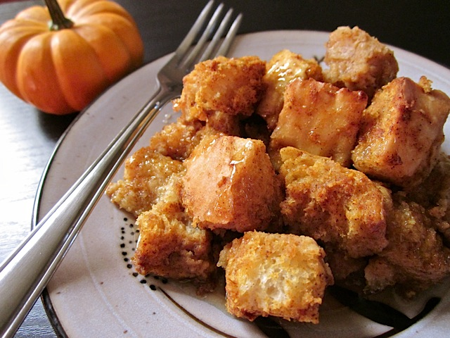 Pumpkin Bread Pudding on plate with fork and staged mini pumpkin on side
