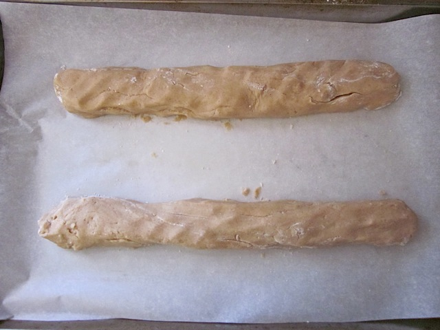 biscotti dough formed into two logs and placed on baking sheet lined with parchment paper