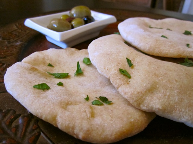 Pita pockets with little plate of olives next to them