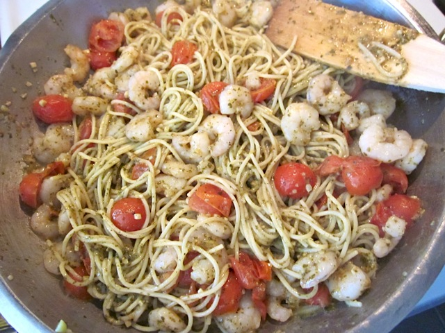 cooked pasta and pesto added to shrimp and tomatoes, all mixed together