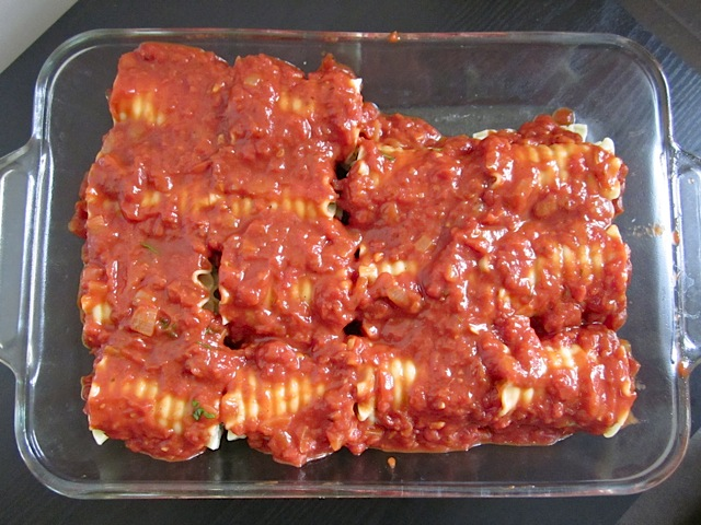 Spinach Lasagna Roll Ups in baking pan covered in sauce