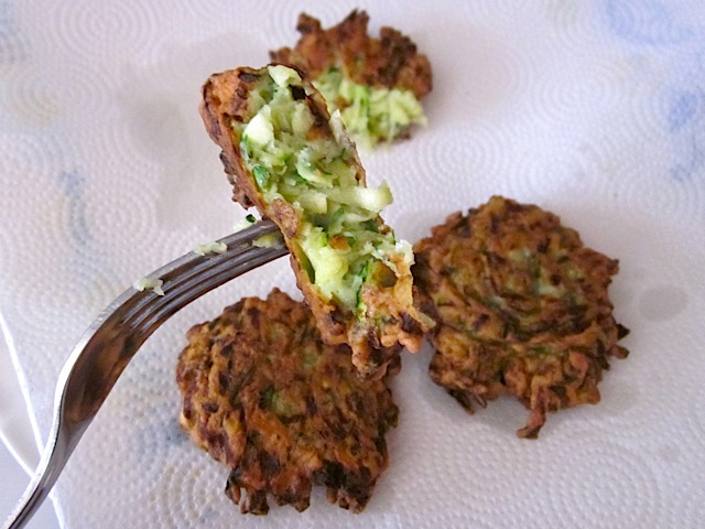 close up of cooked zucchini fritter bite on fork with two whole fritters on side