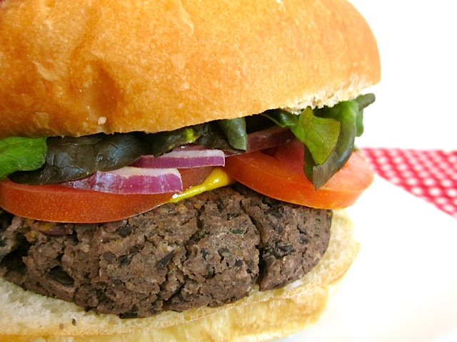 close up side view of a black bean burger with mustard, tomato, red onion, and lettuce.