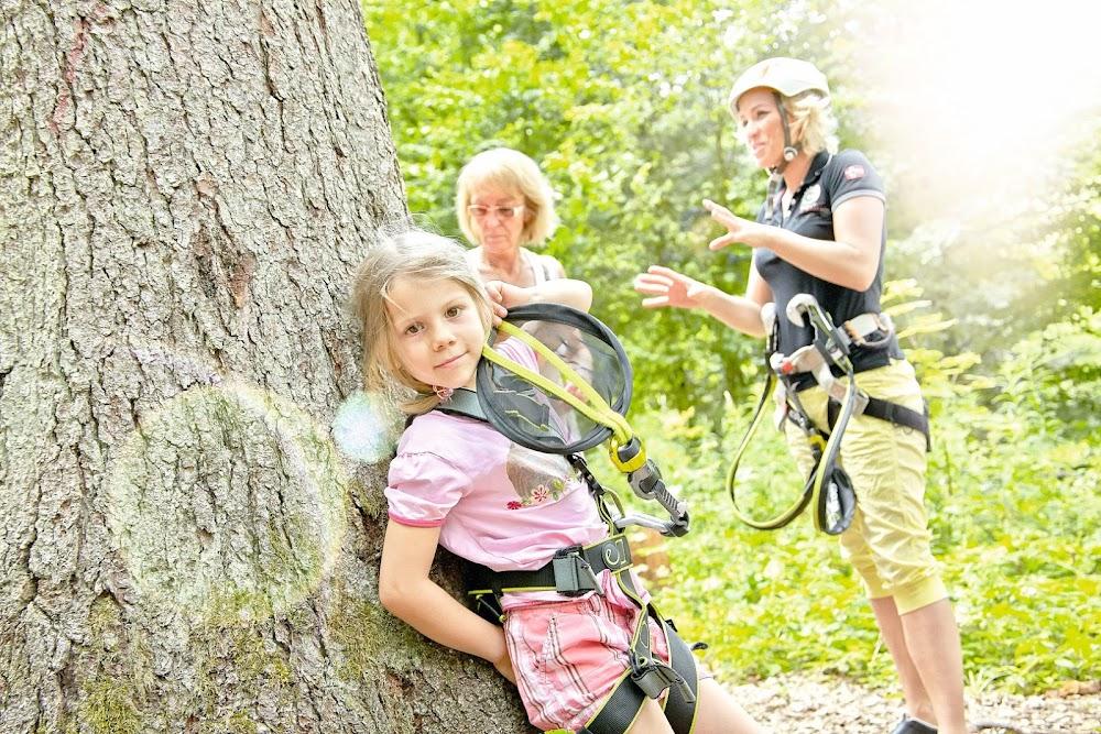 Du siehst ein junges Mädchen, das in ihrer Kletterausrüstung an einem großen Baum lehnt.