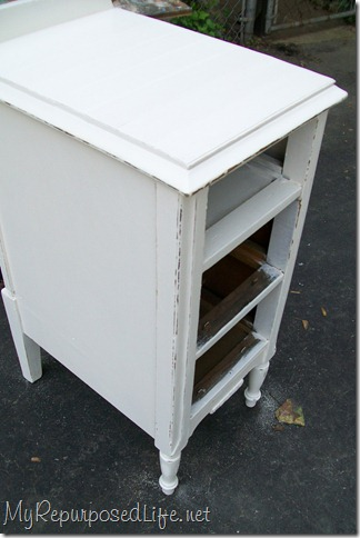 distressing white nightstand with a palm sander
