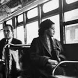 Original Caption: 12/21/1956-Montgomery, AL: Rosa Parks, 43, sits in the front of a city bus here Dec. 21 as a Supreme Court ruling which banned segregation on the city's public transit vehicles took effect. Mrs. Parks' arrest on Dec. 1, 1955, for sitting in a bus forward of white passengers, touched off the boycott of Montgomery Negroes against the city's bus lines.