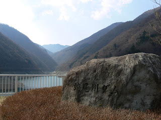 ダム名碑とダム湖を望む